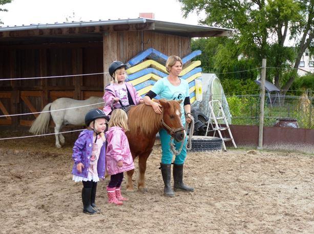 """Nicole Holland-Nell, genannt """"Kolly""""(re.), hat ein Händchen für Kinder und Pferde Im Bild Schulpony """"Prinzi"""" mit Teilnehmern der """"Minis"""""""